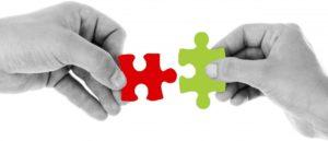 Hände, die Puzzleteile halten, die zusammen passen